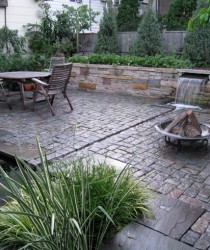 waterfall flows from retaining wall through rill to koi pond