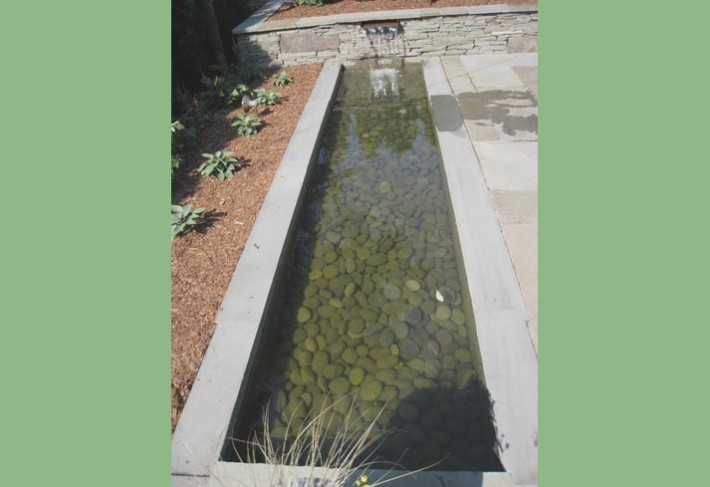 modern reflecting pool with Mexican beach pebbles