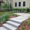 granite sculpture and prairie plantings surround cut stone patio